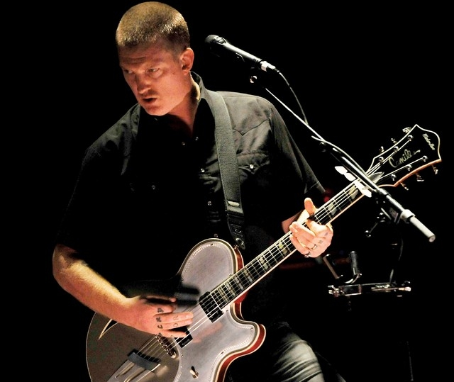 In this Thursday, May 23, 2013 photo, Josh Homme of the band Queens of the Stone Age performs during the band's concert at the Wiltern Theater, in Los Angeles. (Photo by Chris Pizzello/Invision/AP)