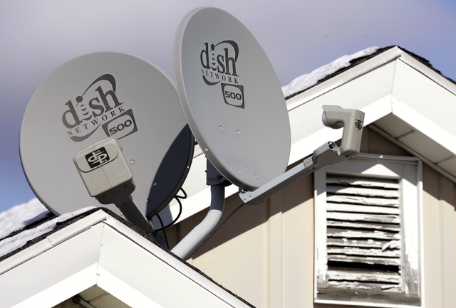 In this Nov. 10, 2008 file photo, Dish Network Corp. satellite dishes are attached to a home in Buffalo, N.Y.  Dish Network and Disney have reached a landmark deal Tuesday, March 4, 2014,  that en ...