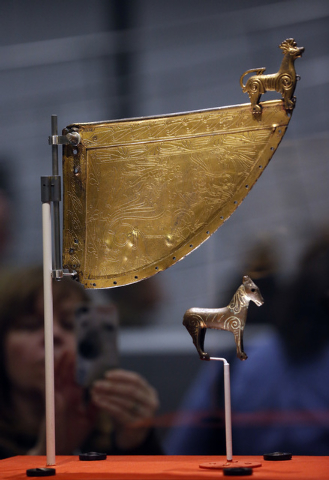 A visitor takes pictures of a Viking horse statuette and a decorated warship weathervane at a new exhibition entitled 'Vikings: Life and Legend' at the British Museum in central London, Tuesday, M ...