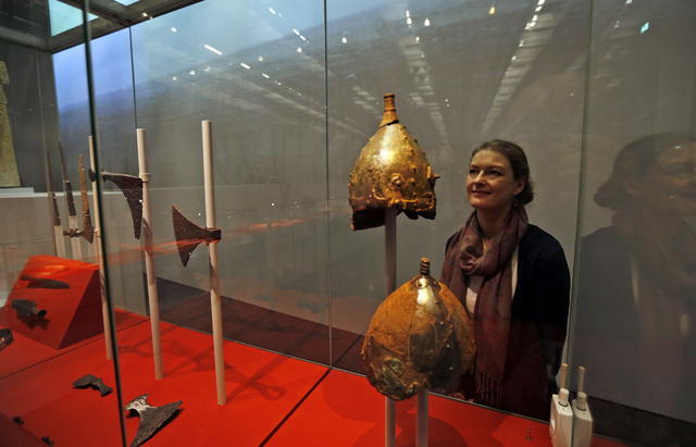 A British museum employee poses for the photographers behind a display of helmets at a new exhibition entitled 'Vikings: Life and Legend' at the British Museum in central London, Tuesday, March 4, ...