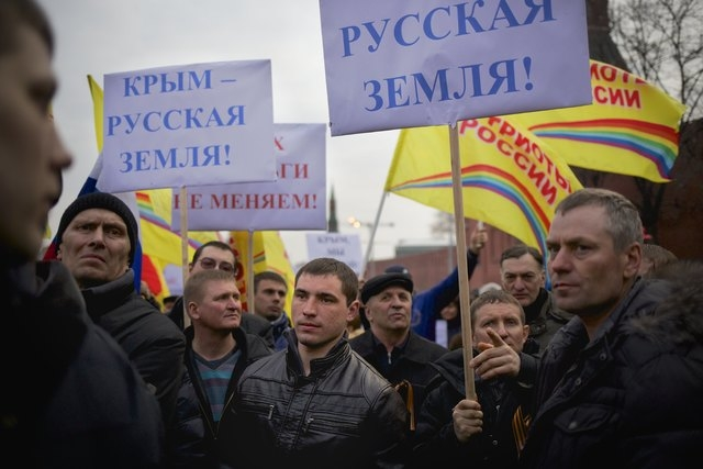 """Pro-Putin demonstrators hold posters reading """"Crimea is Russian land!"""" as they gather towards to Red Square in Moscow on Friday. Russia rallied support Friday for a Crimean bid to secede from Ukra ..."""