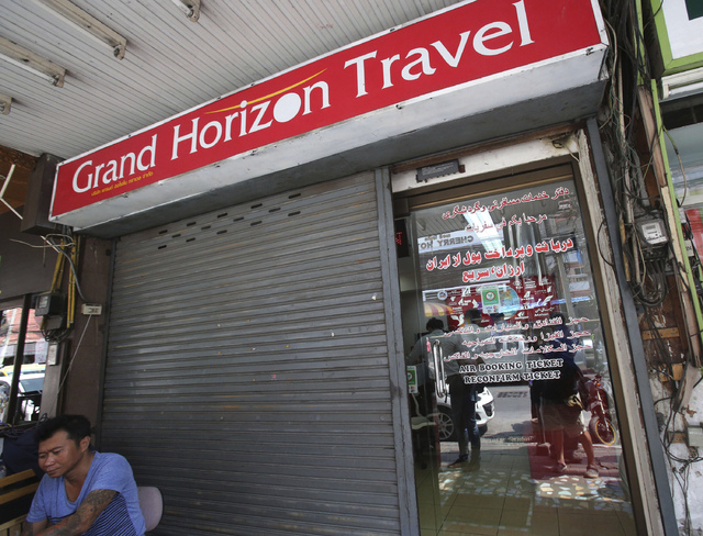 A man sits in front of closed door of the Grand Horizon Travel office in Pattaya, Chonburi province, Thailand, Monday. Thai police said owners of the travel agency told them they had received orde ...