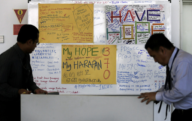 Airport staff move a white board plastered with messages of hope and encouragement to all involved with the missing Malaysia Airlines jet, MH370, at the Kuala Lumpur International Airport on Tuesd ...