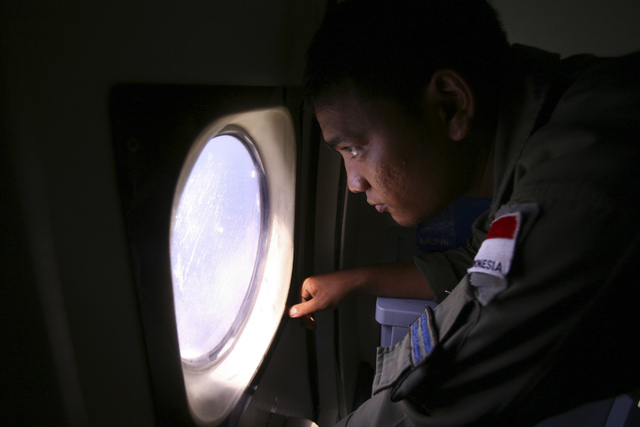 An Indonesian Navy crew member scans the water bordering Indonesia, Malaysia and Thailand during a search operation for the missing Malaysian Airlines Boeing 777 near the Malacca straits on Monday ...