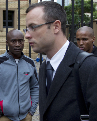 Public Oscar Pistorius, center, arrives at the high court for his trial in Pretoria, South Africa, Tuesday, March 11, 2014. Pistorius is charged with murder for the shooting death of his girlfrien ...