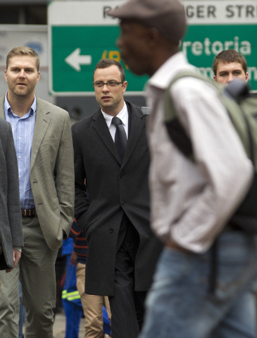 Oscar Pistorius, second from left, accompanied by unidentified men arrives at the high court for his murder trial in Pretoria, South Africa, Tuesday, March 11, 2014. Pistorius is charged with murd ...