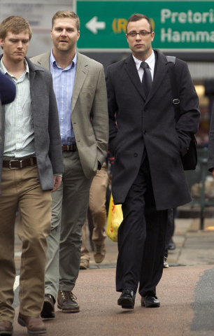 Oscar Pistorius, right, accompanied by unidentified men arrives at the high court for his trial in Pretoria, South Africa, Tuesday, March 11, 2014. Pistorius is charged with murder for the shootin ...