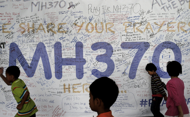 Children run past dedication messages and well wishes displayed for passengers and others involved with the missing Malaysia Airlines jetliner MH370 on the walls of the Kuala Lumpur International  ...