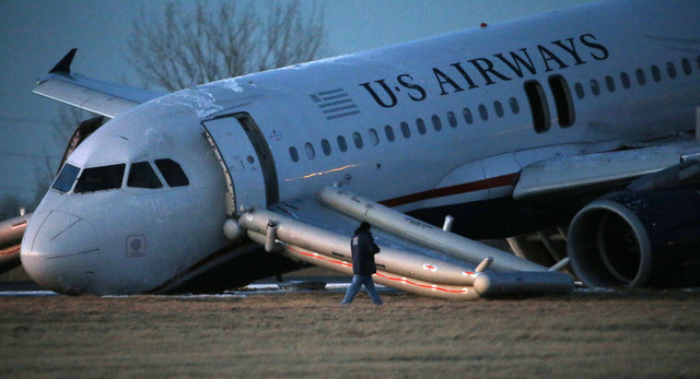 A person walks around a damaged US Airways jet at the end of a runway at the Philadelphia International Airport on Thursday. Airline officials said the flight was heading to Fort Lauderdale, Fla., ...