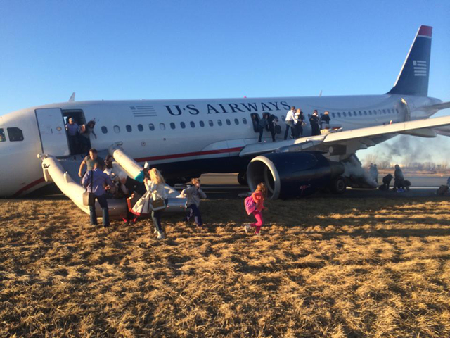 Passengers evacuate US Airways Flight 1702 after the pilot was forced to abort takeoff Thursday evening at Philadelphia International Airport after a tire on the plane's front landing gear blew ou ...