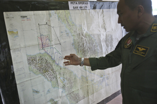 "Lt. Col Bambang Sudewo, commander of the 5th Air Squadron ""Black Mermaids"" examines a map following a search operation for the missing Malaysia Airlines Boeing 777 that was conducted over the Stra ..."