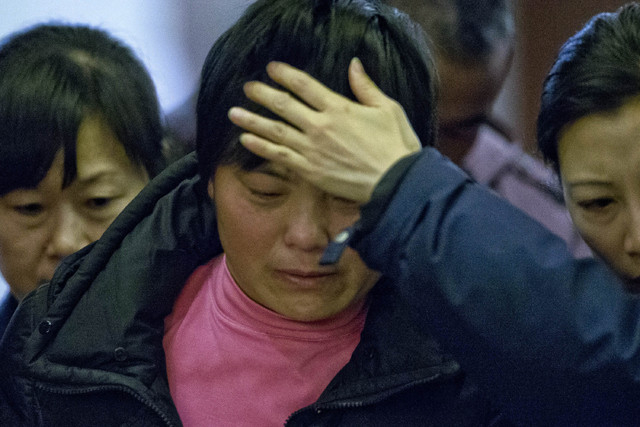 A crying woman, one of the relatives of Chinese passengers aboard missing Malaysia Airlines Flight MH370, is assisted by volunteers as she leaves a hotel ballroom where families were briefed on re ...