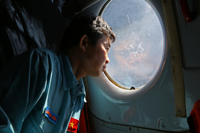 Officer Lang Van Ngan of the Vietnam Air Force looks out the window onboard a flying AN-26 Soviet made aircraft during a search operation for the missing Malaysia Airlines flight MH370 plane over  ...