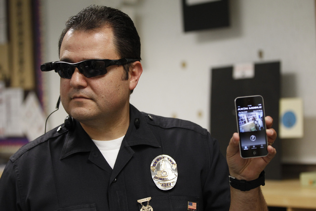 This Jan. 15, 2014 file photo shows Los Angeles Police Sgt. Daniel Gomez demonstrating a video feed from his camera into his cellphone as on-body cameras are demonstrated for the media in Los Ange ...