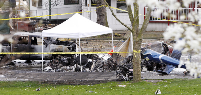 Caution tape surrounds the charred wreckage of a news helicopter and two vehicles after the chopper crashed into a city street near the Space Needle, Tuesday, March 18, 2014, in Seattle. Two peopl ...