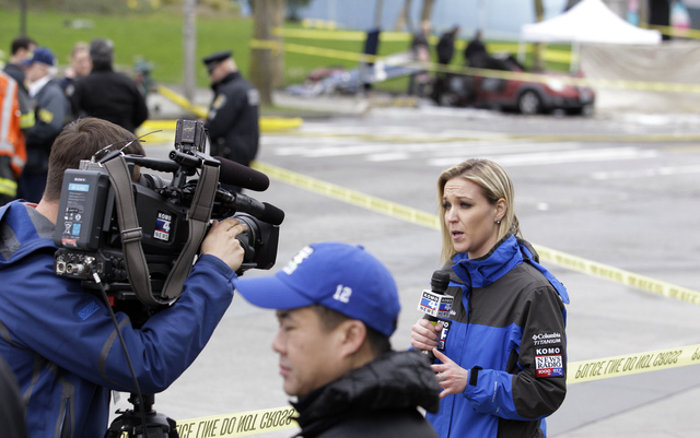 KOMO broadcaster Kelly Koopmans, right, works at the scene of the crash of a KOMO news helicopter Tuesday, March 18, 2014, in Seattle.  The helicopter helicopter crashed into a city street near Se ...