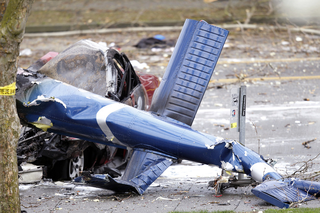 The wreckage of a news helicopter sits on a city street after crashing Tuesday, March 18, 2014, in Seattle. A news helicopter crashed into a city street near Seattle's Space Needle on Tuesday, kil ...