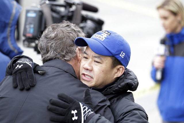 KOMO assignment editor Norm Mah, right, gets a hug as he works at the scene of the crash of a KOMO news helicopter Tuesday, March 18, 2014, in Seattle. A KOMO-TV helicopter helicopter crashed into ...
