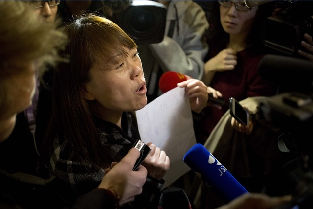 """A relative of a Chinese passenger aboard the missing Malaysia Airlines Flight MH370 holds a paper which reads """"Hunger strike protest, Respect life, Return my relative, Don't want become victim of  ..."""
