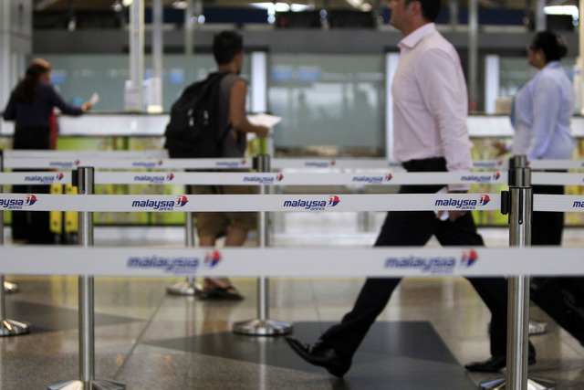 Passengers walk to check in at Malaysia Airlines counters at Kuala Lumpur International Airport in Sepang, Malaysia, on Tuesday. Checks into the background of all the Chinese nationals on board th ...