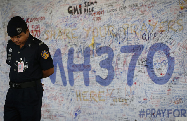 Malaysia airport police officer stands in front of  messages board for the passengers aboard a missing Malaysia Airlines plane at Kuala Lumpur International Airport in Sepang, Malaysia, Wednesday. ...