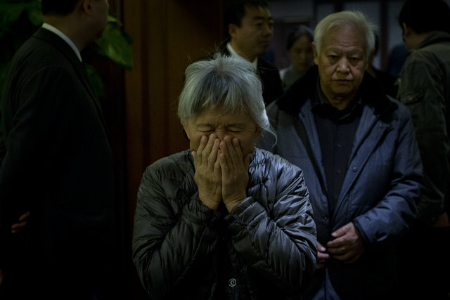 An elderly woman, one of the relatives of Chinese passengers aboard missing Malaysia Airlines Flight MH370, covers her face out of frustration as she leaves a hotel ballroom after a daily briefing ...