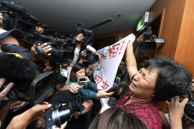 A Chinese relative of passengers aboard a missing Malaysia Airlines plane cries as she holds a banner in front of journalists reading 'We are against the Malaysian government for hiding the truth  ...