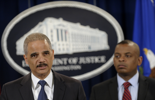 Attorney General Eric Holder, left, accompanied by Transportation Secretary Anthony Foxx, announces a $1.2 billion settlement with Toyota over its disclosure of safety problems during a news confe ...