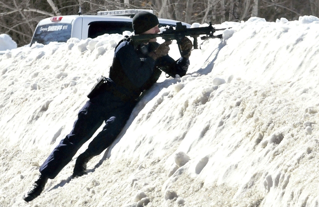 In this Tuesday, March 18, 2014 photo, trooper Scott Duff trains his rifle toward the home of Michael Smith in Norridgewock, Maine. Officers descended on Smith's home after members of a tree remov ...