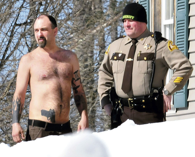 In this Tuesday, March 18, 2014 photo, Michael Smith, left, stands beside a Somerset County Sheriff deputy outside his home in Norridgewock, Maine. Officers armed with assault rifles descended on  ...