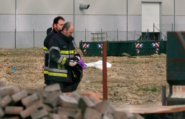 Emergency personnel remove evidence near a covered body after a World War I armament exploded in Ypres, Belgium on Wednesday. According to the Belgian Defense Department, two construction workers  ...
