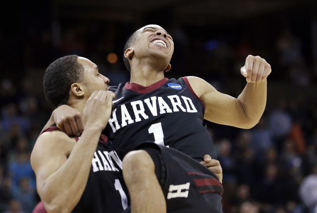Harvard's Siyani Chambers, right, leaps into the arms of teammate Brandyn Curry after the team beat Cincinnati in the second round of the NCAA college basketball tournament in Spokane, Wash., Thur ...