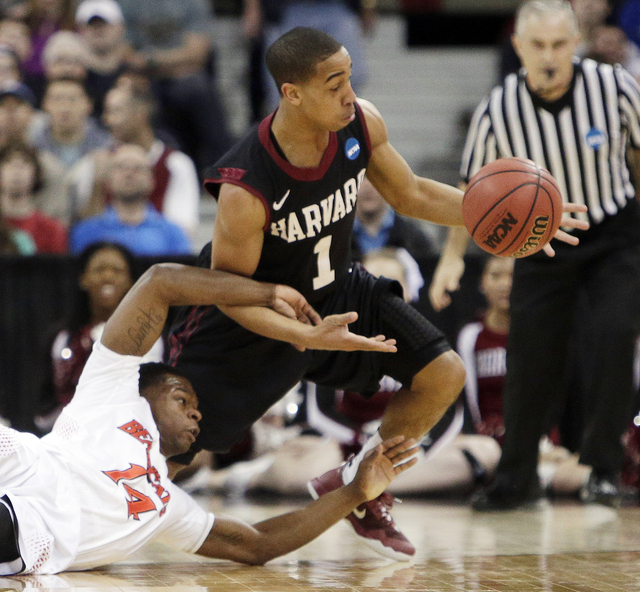 Harvards Siyani Chambers (1) and Cincinnatis Ge'Lawn Guyn (14) fight for a loose ball in the second half during the second-round of the NCAA college basketball tournament in Spokane, Wash., Thursd ...