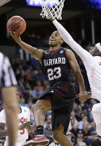 Harvard's Wesley Saunders (23) drives the last past Cincinnati's Justin Jackson in the second half during the second round of the NCAA college basketball tournament in Spokane, Wash., Thursday, Ma ...