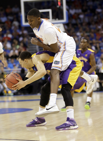 Florida forward DeVon Walker (25) goes over Albany forward Gary Johnson (20) during the first half in a second-round game in the NCAA college basketball tournament Thursday, March 20, 2014, in Orl ...