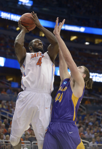 Florida center Patric Young (4) drives to the basket over Albany center John Puk (44) during the first half of a second-round game in the NCAA college basketball tournament on Thursday, March 20,  ...
