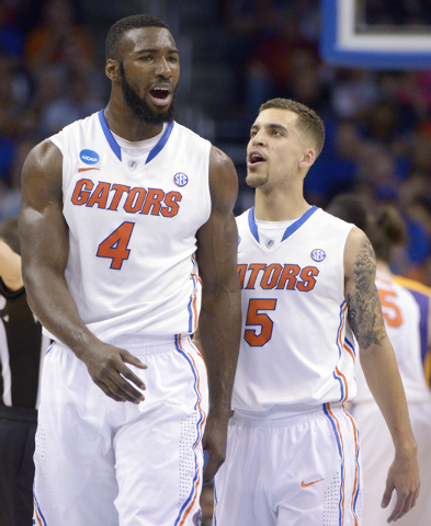 Florida guard Scottie Wilbekin (5) and center Patric Young (4) talk on the court during the second half in a second-round game against Albany in the NCAA college basketball tournament against Alba ...