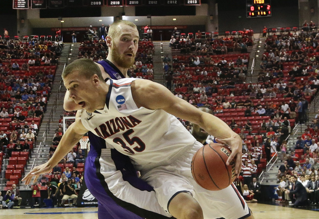 Arizona center Kaleb Tarczewski spins around Weber State center Kyle Tresnak while going to the basket during the first half in a second-round game in the NCAA college basketball tournament Friday ...