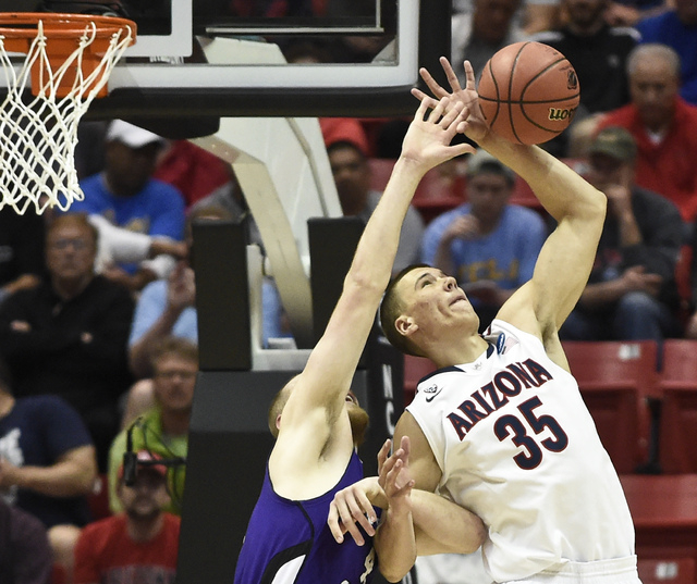 Arizona center Kaleb Tarczewski battles with Weber State center Kyle Tresnak for a rebound during the first half in a second-round game in the NCAA college basketball tournament Friday, March 21,  ...