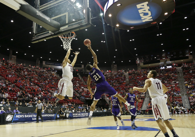 Weber State forward Joel Bolomboy (21) gets up in the air to block a lob pass intended for Arizona guard Nick Johnson, left, during the first half in a second-round game in the NCAA college basket ...
