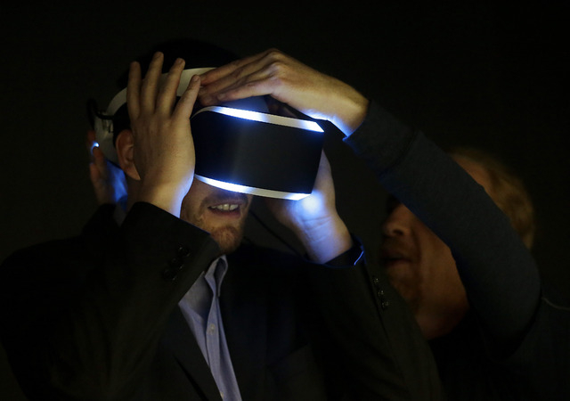Kevin Joyce, left, gets help putting on the PlayStation 4 virtual reality headset Project Morpheus in a demo area at the Game Developers Conference 2014 in San Francisco, Wednesday, March 19, 2014 ...