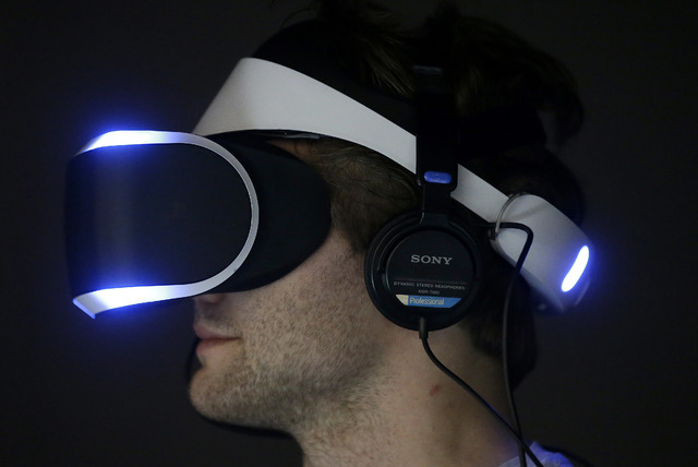 Marcus Ingvarsson tests out the PlayStation 4 virtual reality headset Project Morpheus in a demo area at the Game Developers Conference 2014 in San Francisco, Wednesday, March 19, 2014.  (AP Photo ...