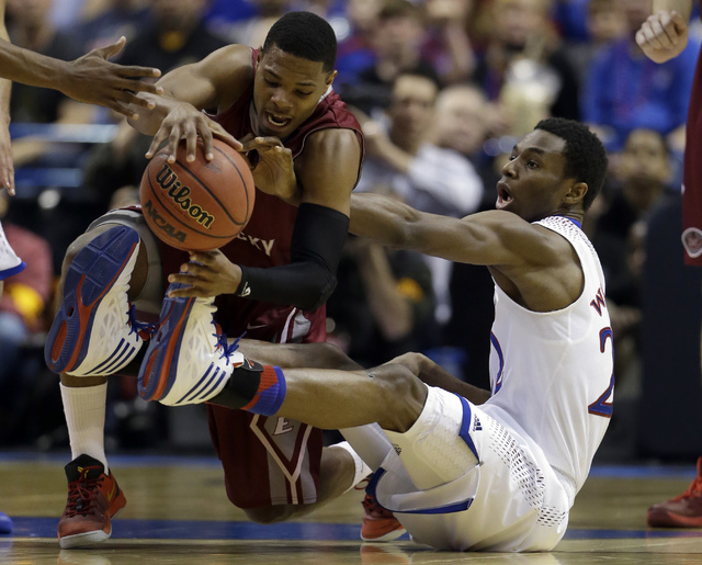 Eastern Kentucky's Corey Walden, left, and Kansas' Andrew Wiggins get tangled up while chasing after a loose ball during the first half of a second-round game in the NCAA college basketball tourna ...