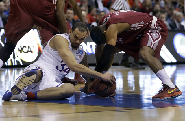 Kansas' Perry Ellis, left, and Eastern Kentucky's Corey Walden fight over a loose ball during the first half of a second-round game in the NCAA college basketball tournament Friday, March 21, 2014 ...
