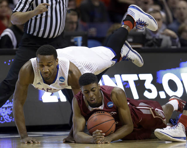 Eastern Kentucky's Marcus Lewis, right, and Kansas' Wayne Selden, Jr. dive after a loose ball during the first half of a second-round game in the NCAA college basketball tournament Friday, March 2 ...