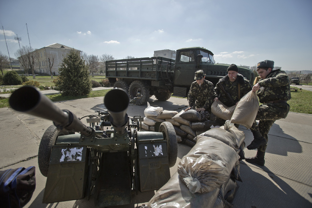 Ukrainian airmen place sand bags around an anti-aircraft gun at the Belbek air base, outside Sevastopol, Crimea, Friday, March 21, 2014. Congress last week neared completion of legislation that wo ...