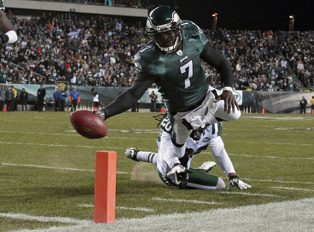 FILE - In a Dec. 18, 2011 file photo, Philadelphia Eagles quarterback Michael Vick (7) scores a touchdown in the first half of an NFL football game, in Philadelphia. The New York Jets signed quart ...
