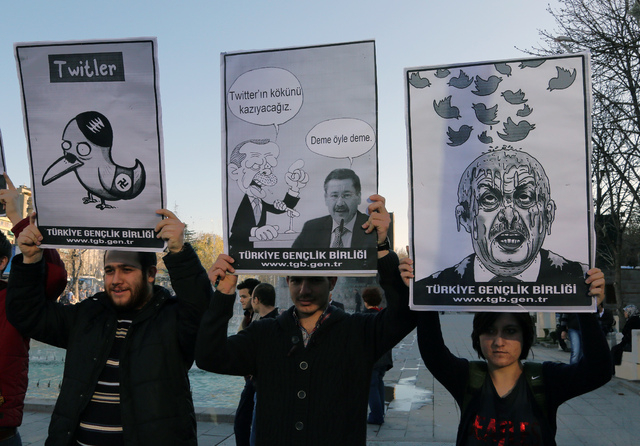 Members of the Turkish Youth Union hold cartoons depicting Turkey's Prime Minister Recep Tayyip Erdogan during a protest against a ban on Twitter, in Ankara, Turkey, Friday, March 21, 2014. Turkey ...
