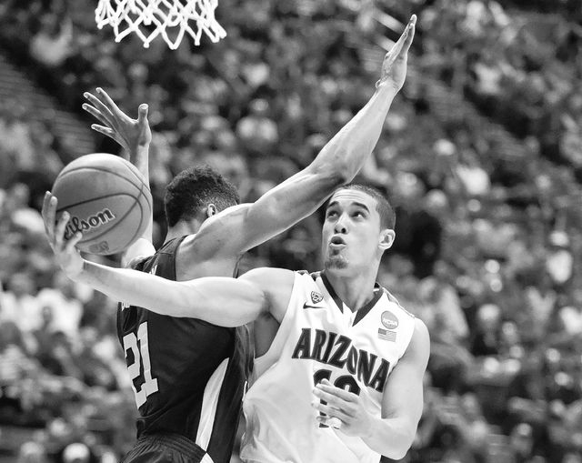 Arizona's Nick Johnson gets a shot off under the arm of Weber State's Joel Bolomboy during the second half in a second-round game in the NCAA college basketball tournament Friday, March 21, 2014,  ...