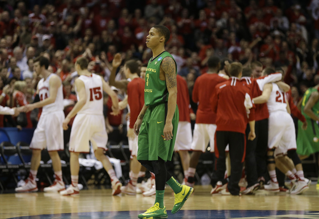 Oregon guard Joseph Young (3) walks off as Wisconsin celebrates after defeating Oregon 82-77 in a third-round game of the NCAA college basketball tournament Saturday, March 22, 2014, in Milwaukee. ...
